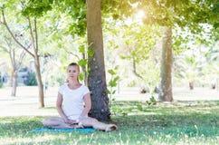 Giovane donna sveglia che allunga nel parco Fotografia Stock Libera da Diritti