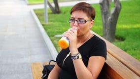 Giovane donna sveglia che beve limonata fresca sul banco nel parco stock footage