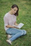 Giovane donna sveglia che legge il libro Immagine Stock