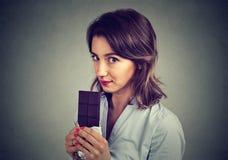 Giovane donna sveglia che mangia un cioccolato fotografie stock libere da diritti