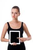 Giovane donna sveglia che mostra lo schermo in bianco della compressa Fotografie Stock