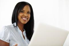 Giovane donna sveglia che per mezzo di un computer portatile Fotografia Stock