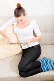 Giovane donna sveglia che si rilassa sullo strato Immagini Stock