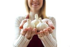 Giovane donna sveglia che tiene gli spicchi d'aglio in entrambe le mani su bianco fotografia stock libera da diritti