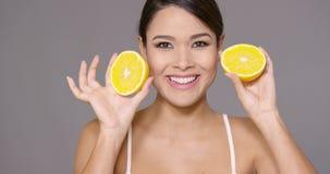 Giovane donna sveglia che tiene un'arancia fresca divisa in due video d archivio