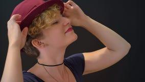 Giovane donna sveglia con capelli biondi ricci che giocano con il suo cappello e che sorridono, isolata su fondo nero video d archivio