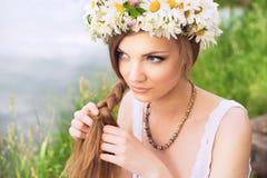 Giovane donna sveglia con il cerchietto della camomilla che intreccia i suoi capelli alla t Fotografie Stock