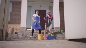 Giovane donna sveglia ed uomo che ballano sul portico della casa Coppia fare piazza pulita insieme Vita sistematica felice stock footage