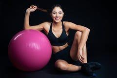 Giovane donna sveglia felice di forma fisica che si siede con il fitball porpora Immagini Stock