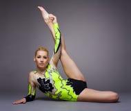 Giovane donna sveglia nel vestito del gymnast che fa spaccatura Fotografia Stock