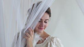 Giovane donna sveglia Tulle aperta e vicino timido del ritratto il suo fronte con il fan della piuma bianca sul mezzo fronte del  video d archivio