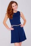 Giovane donna sveglia in vestito dall'azzurro di blu marino su bianco Fotografia Stock