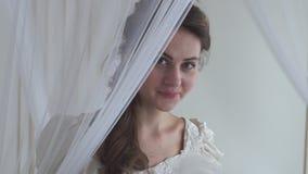 Giovane donna sveglia vicino al fan d'ondeggiamento della piuma bianca di Tulle La ragazza porta il vestito bianco ed ha bello st stock footage