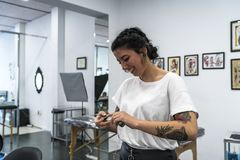 Giovane donna tatuata preparando la macchina del tatuaggio fotografia stock libera da diritti