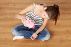 Giovane donna teenager con la sua banca piggy dentellare Fotografia Stock