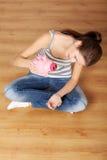 Giovane donna teenager con la sua banca piggy dentellare Immagine Stock Libera da Diritti