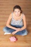 Giovane donna teenager con la sua banca piggy dentellare immagini stock libere da diritti