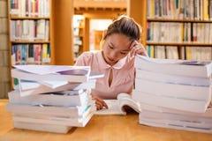 Giovane donna tesa che studia nella biblioteca Immagine Stock Libera da Diritti