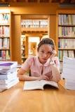 Giovane donna tesa che studia nella biblioteca Immagini Stock