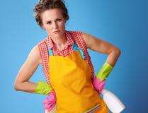 Giovane donna tesa con la spugna di pulizia e detersivo sul blu immagini stock libere da diritti
