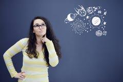 Giovane donna thinkful sul fondo di gray blu con le icone di universum Fotografia Stock Libera da Diritti