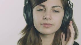Giovane donna triste attraente che ascolta la musica sulle cuffie stock footage