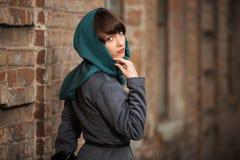 Giovane donna triste in cappotto classico alla parete immagini stock