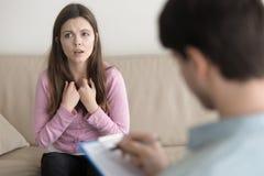 Giovane donna triste che dice circa il suo problema agli psychotherapis maschii Immagini Stock