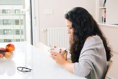 Giovane donna triste che mangia prima colazione Fotografia Stock