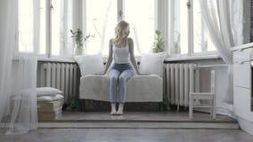 Giovane donna triste che si siede e che pensa sul sofà davanti alle grandi finestre del suo appartamento luminoso azione Biancher stock footage