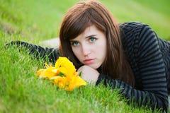 Giovane donna triste che si trova sull'erba Fotografia Stock