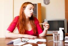 Giovane donna triste con i farmaci a casa in salone dietro la t Fotografia Stock Libera da Diritti
