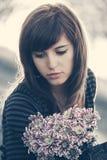Giovane donna triste con il sogno di giorno dei fiori all'aperto Immagine Stock Libera da Diritti