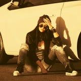 Giovane donna triste dei pantaloni a vita bassa di modo che si siede accanto alla sua automobile fotografia stock libera da diritti