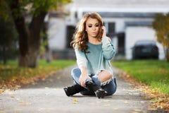 Giovane donna triste di modo che si siede sulla via della città Immagine Stock