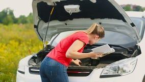 Giovane donna turbata che esamina l'automobile manuale e che prova a riparare il veicolo del brakedown sulla strada abbandonata video d archivio