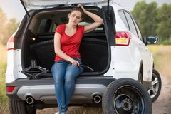 Giovane donna turbata che si siede nel tronco di automobile aperto sulla strada abbandonata alla campagna ed all'aiuto aspettante Fotografie Stock Libere da Diritti