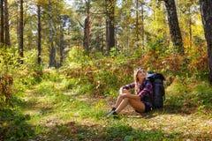 Giovane donna turistica bionda con uno zaino che si siede sul sidel immagine stock libera da diritti