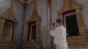 Giovane donna turistica che fa foto con il telefono cellulare del tempio buddista tailandese stock footage