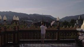 Giovane donna turistica che fa foto con il telefono cellulare del tempio buddista tailandese archivi video