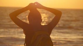 Giovane donna turistica che lega coda di cavallo sulla spiaggia vicino al mare al tramonto La bella ragazza schiaccia i suoi cape fotografia stock libera da diritti