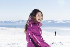 Giovane donna turistica che ride in una montagna di inverno Immagine Stock