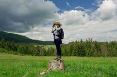 Giovane donna turistica che sta su un ceppo di albero con una macchina fotografica a disposizione, facendo le immagini della foto Fotografia Stock