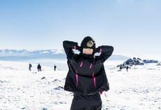 Giovane donna turistica con a braccia aperte in una montagna di inverno Fotografie Stock