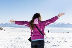 Giovane donna turistica con a braccia aperte in una montagna di inverno Immagini Stock Libere da Diritti