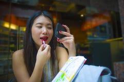 Giovane donna turistica coreana asiatica felice ed attraente che si siede alla caffetteria della città facendo uso del trucco del fotografia stock