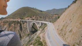Giovane donna turistica di vista posteriore con lo zaino ed i capelli volanti che guarda paesaggio epico al punto del ponte del c stock footage