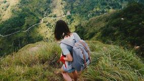 Giovane donna turistica felice con lo zaino che fa un'escursione giù il percorso ripido pericoloso, Mountain View epico nel movim stock footage