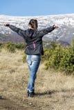Giovane donna turistica in una montagna di inverno con a braccia aperte - la Bulgaria Fotografia Stock Libera da Diritti
