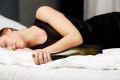 Giovane donna ubriaca che dorme sul letto fotografia stock
